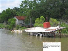 Vessel sunken at the dock, roof line visible above the water line