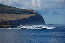 The eternal battle of surf and shore.  The seemingly soft water will eventuallywin. View of an impressive Easter Island volcanic headland.
