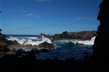 A small hole-in-the wall affords a glimpse of azure surf pounding againstagainst jagged volcanic rocks.