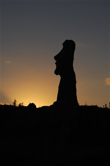 A moai silhouetted in one of the thousands of sunsets that have occurredsince its being placed on the rocky shores of Easter Island.