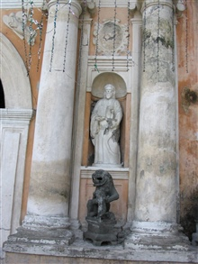 A gargoyle statue and a saint statue adorning San Augustin Church.
