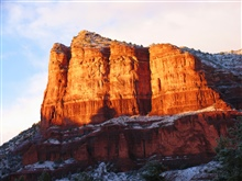 Late afternoon sun illuminates a red rock mesa with a dusting of snow.