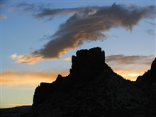 A castle-like rock structure silhouetted in the sunset
