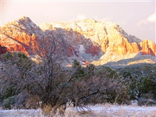 A majestic scene of sandstone mountains dusted with snow and valley oaks andpinion pines