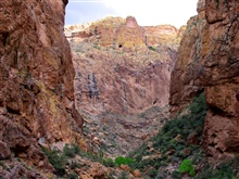 Sandstone cliffs, perhaps a lost mine on the cliff high above, and desertfoliage in the canyon bottoms.
