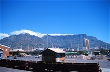 Table Mountain with clouds forming on top .  A local saying describes thiseffect as Table Mountain with its cloud tablecloth.