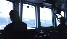 Ensigns Angie Messer and Angie Venturato keep a sharp lookout during a storm inthe Gulf of Alaska.