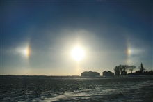 The suspension of ice crystals in the lowest levels of the atmosphere helpedcreate this optical display of parhelias across the Iowa landscape.