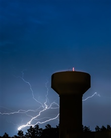 A strong lightning bolt coming from behind the trees; appearing to be reachingout for the water tower.