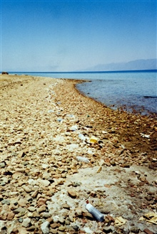 Plastic litter finds its way into the Gulf of Aqaba and lines a cobble beach.