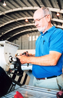 Roy DeHart working on Bell 212 helicopter
