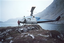 Bell helicopter landing in precarious position.  Note rear of port skid hangingover cliff.  Helicopter support of geodetic operations along the AlaskaPeninsula.