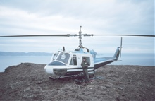 Helicopter mechanic alongside Bell helicopter supporting geodetic operations onthe Alaska Peninsula.