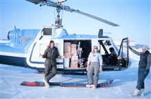 Brendan Kelley and Lori Quackenbush of the University of Alaska Fairbanks andNOAA helicopter mechanic Russ Talley (on right) loading Bell UH-1M withgear for remote camp from Reindeer Island.