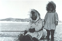 Eskimo woman and child ice fishing in the Bering Sea
