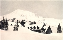 Paradise Inn looking north toward the summit of Mount Rainier.  In the winter of 1916-1917, 789.5 inches of snow fell at Paradise Inn.  At the time of the photo, the snow was approximately 27 feet deep.In:  Monthly Weather Review, July 1918, p. 330.