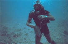 A diver equipped with underwater tape recorder, wetsuit, watch for determining dive time.