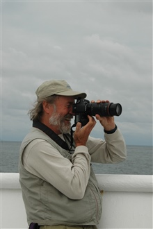 Ed Bowlby, Research Coordinator for the Olympic Coast National MarineSanctuary, photographing humpback whales feeding just off the bow of theNOAA Ship McARTHUR II.