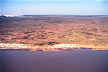 Grand Bay National Estuarine Research Reserve.North over Mississippi Sound showing eroding shoreline and high marsh, Point aux Chenes, southwestern portion of reserve.  Mississippi Phosphate Company waste gypsum stack visible to northwest.  Taken dur