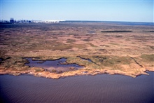 Grand Bay National Estuarine Research Reserve.North over Mississippi Sound showing eroding shoreline and high marsh, Point aux Chenes, southwestern portion of reserve.  Mississippi Phosphate Company waste gypsum stack visible to northwest.  LSU aeria
