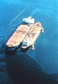 EXXON VALDEZ aground on Bligh Reef being lightered to reduce oil spillage andlighten ship to get off reef.