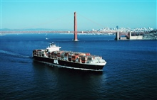 An outward bound containership with the Golden Gate and SanFrancisco skyline in the background.