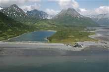 Aerial photograph. A rectangular lake, majestic mountains, the low tide lineapproximately 20 feet vertically below the logs and debris marking high tide.