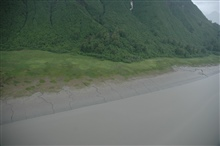 Aerial photograph. the continuation of streams running off a steepmountainside into the tidal zone is apparent.  Note the very pronouncedmeander in the center-right steam.