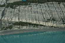 Aerial photograph. Eroding sedimentary layers reflecting in blue-green waters.