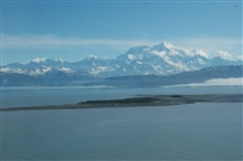 Aerial photograph. Mount St. Elias see over an offshore island in theGulf of Alaska.