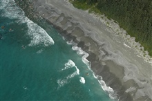 Aerial photograph.  Magnificent forest, driftwood, and a gray sand beachwith rocky offshore washed by gentle surf.