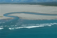 Aerial photograph. A river cuts through the sandy beach on the south end of theDry Bay area.