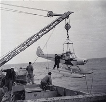 Loading a stripped down Piper Cub on the PIONEER.Plane used to tend tide gages and do reconnaissance