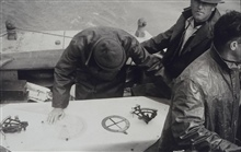 Checking boatsheet during wiredrag survey of Mitchell Jordan Reservoir.Plastic three-arm protractor for plotting fixes barely visible under hand.Surveying reservoir for seaplane landing site during WWII ferrying operations.Wiredrag party of Max G. Ri