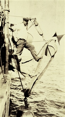 Planting anchor for Radio Acoustic Ranging hydrophone.Must have been warm -  note bare foot helping push anchor away from ship