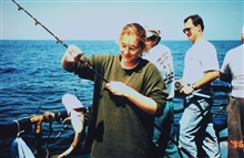 Young woman displaying her first fish of the day, an Atlantic Cod.  Sheoutfished most of the boat that day.