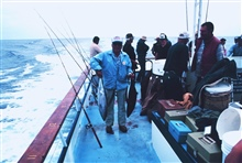 Happy angler displays two albacore tuna aboard charter (CPFV) vessel