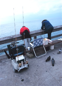 Local piers provide access to recreational fishing for thousands throughout theUnited States.  Here two fishermen are trying for Pacific mackerel off theNewport Pier on a foggy day.