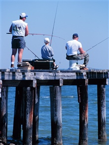 Fishing off a weather-beaten pier at Westland Beach