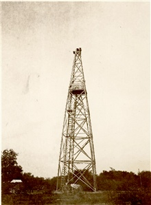 A large wooden tower with wagon below and man at top for scale.