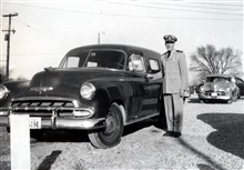 LCDR Edmund Jones ready to step into a U. S. Government Chevrolet panel truckused by geodetic survey crews.