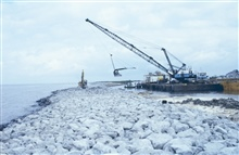 A barge-mounted crane loads rock which will be placed to stabilize shorelineerosion.