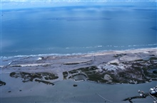 An aerial view looking out toward the Gulf of Mexico. The oil fieldinfrastructure can be clearly seen in the lower right hand corner of thephotograph.