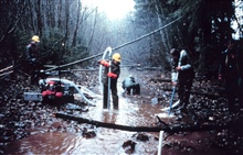 Three men in the river operate the pump.