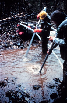 A close-up of air being pumped into the floor of the riverbed to loosensediments.