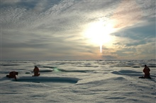 Scientists work on ice over the deep Arctic Ocean.
