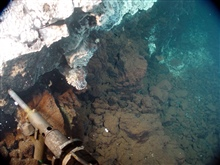Pacific Ring of Fire Expedition. Sampling hydrothermal vent fluids at Cavevent, using the Hot Fluid Sampler (HFS).  The white coating on the rocks isbacterial mat.  The sampling nozzel is 25 cm (10 in).