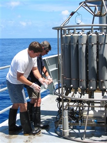 Pacific Ring of Fire Expedition. Geoff Lebon (foreground) and Ed Baker(background) are removing plume water from the CTD bottles after a tow-yo.