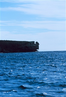 From the water, a prominent cliff face of Mona Island