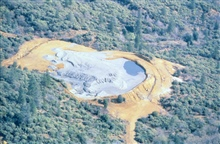A containment facility or tailings impoundment area. The upper portion of theimage shows where the tailings are dumped.